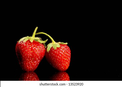 Two strawberries on black background, lots of copy space