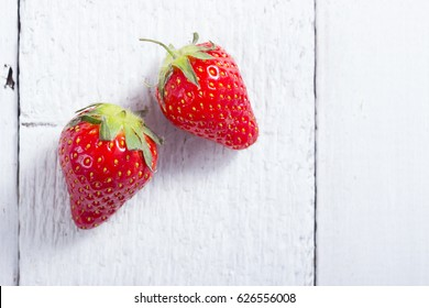 two strawberry fruits on white wood table background