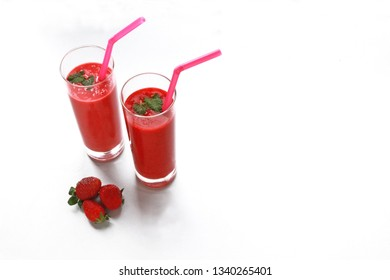two strawberry smoothies and some strawberries on white background