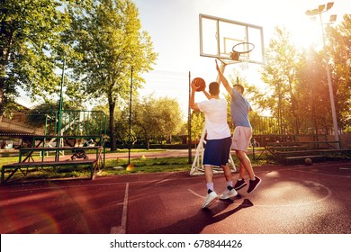 Two street basketball players having training outdoor. They are making a good action.
