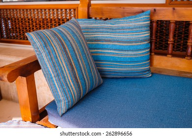 Two striped cushions lie on a wooden sofa.