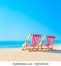 Two striped red-white sunbeds at sandy tropical ocean beach in hot sunny day. Natural travel background. Tourist relaxation concept.