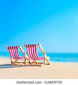 Two striped red-white sunbeds at sandy tropical ocean beach in hot sunny day. Natural travel background. Tourist chillout concept.