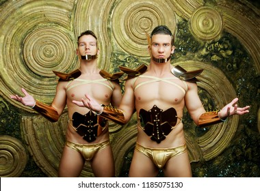 two striptease dancers wearing costumes with golden armour in the studio against golden studio background