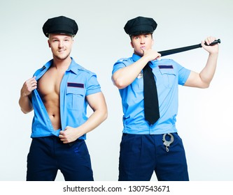 two striptease dancers wearing costumes of policemen in the studio