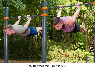 Two strong handsome young athletes hanging belly-down parallel to the floor, having street workout, doing exercises for fitness and health on sunny day in summer.