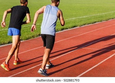 Two strong healthy men jogging on athletics track in summertime