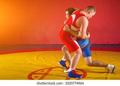 Two strong wrestlers in blue and red wrestling tights are wrestlng and doing grapple on a yellow wrestling carpet in the gym.
