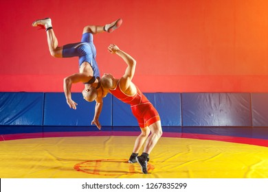 Two strong wrestlers in blue and red wrestling tights are wrestlng and making a suplex wrestling on a yellow wrestling carpet in the gym. Young man doing grapple.