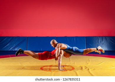 Two strong wrestlers in blue and red wrestling tights are wrestlng and do push-ups and gymnastic exercises in pairs, plank in the gym. Young man doing grapple.
