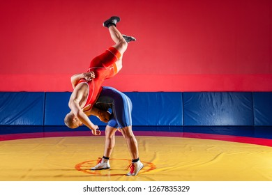 Two strong wrestlers in blue and red wrestling tights are wrestlng and making hip throw wrestling on a yellow wrestling carpet in the gym. Young man doing grapple.