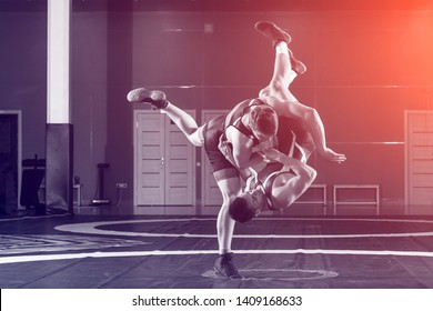 Two strong wrestlers in blue and red wrestling tights are wrestlng and making a  making a hip throw  on a wrestling carpet in the gym. Young man doing grapple.
