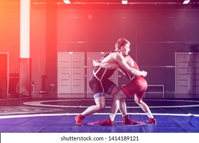 Two strong wrestlers in blue and red wrestling tights are wrestlng and making a  making a hip throw  on a yellow wrestling carpet in the gym. Young man doing grapple.