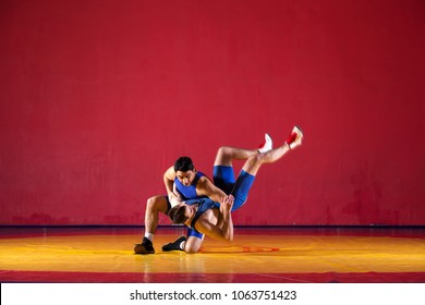 Two strong wrestlers in blue  wrestling tights are wrestlng and making a  making a hip throw  on a yellow wrestling carpet in the gym. Young man doing grapple.