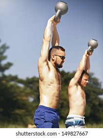 Two strong young men lifting heavy kettlebell weights