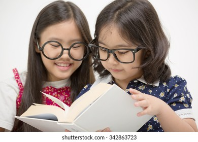 Two student little Asian girls reading the book on isolated