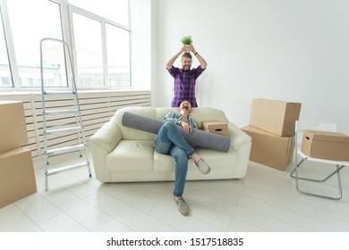 Two student male friends holding their things in their hands sitting in the living room of a new apartment. Housewarming concept