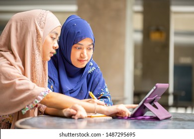 Two student muslim looking tablet for study in university