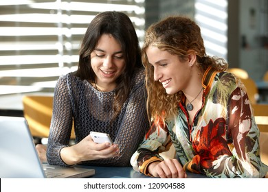 Two students looking at a mobile phone