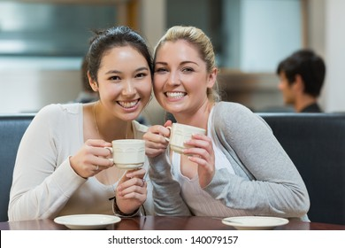 Two students sitting in college coffee shop while drinking and holding a cup of coffee