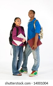 Two students stand and look at the camera with happy expressions on their faces. They wear backpacks and he carries a notebook. Vertically framed photograph.