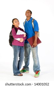 Two students stand and look at the camera while laughing. They wear backpacks and he carries a notebook. Vertically framed photograph.