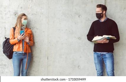 Zwei Studierende, die sich mit einer Gesichtsmaske im sozialen Bereich gegenseitig anschauen