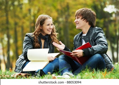 Two students studying in park on grass with notebook outdoors