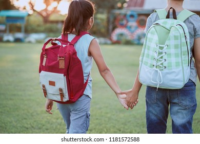 Two students walk hand in hand go to school in the morning