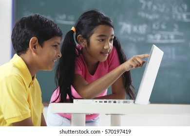 two students working at laptop
