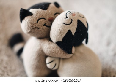 Two stuffed cats hugging each other