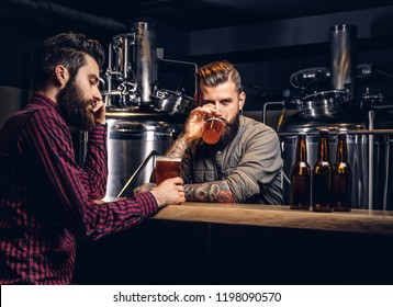 Two stylish bearded hipsters friends drinking craft beer together at the indie brewery.