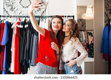 Two stylish and beautiful girls with proffesional make up taking self portrait at smart phone near clothes. Trendy women smiling and posing at store with clothes. Concept of shoping.