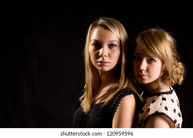 Two stylish blonde teenage girls posing close together in the darkness of nightclub, head and shoulders portrait with copyspace