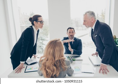 Two stylish business persons in suits having disagreement, war, conflict, standing near desktop in front of each other, face to face with disrespect expression, partner showing stop sign with hands