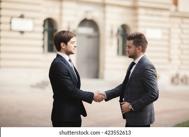 Two stylish businessmen shaking hands in suits