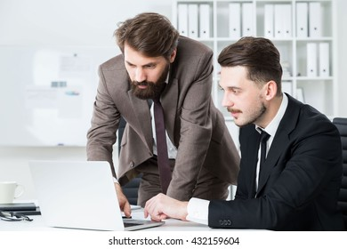 Two stylish businessmen sitting and standing at office desk discussing business project on laptop