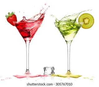 Two stylish cocktail glasses with fruity liquor splashing out, garnished with a ripe fresh strawberry and kiwi, closeup isolated on white. Party concept.