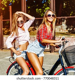 Two stylish girls having fun sitting on a bicycle