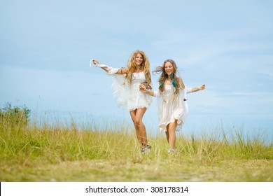 two stylish girls running on the field