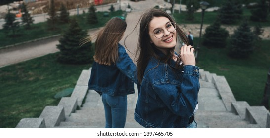 Two stylish happy girls best friends walking in the city park looking at camera