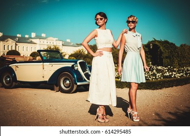 Two stylish ladies near classic convertible