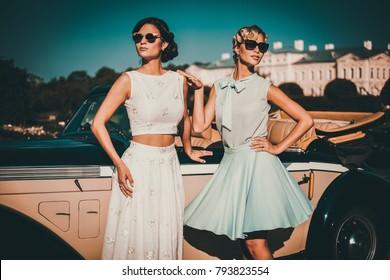 Two stylish ladies near classic convertible.