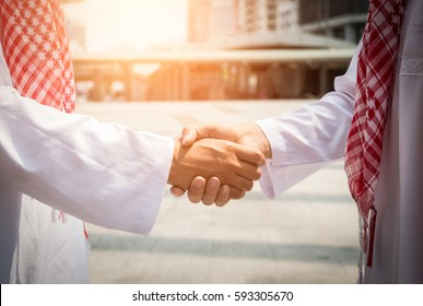 Two successful arabic businessman shaking hands over a deal in the modern city.