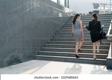 Two successful Asian business women walking on the stairs and chat with each other. Both wearing formal suits and high hills .one carrying tablet one carrying bag.