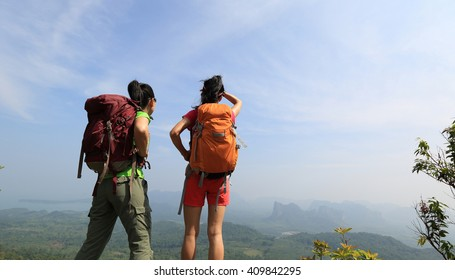 two successful backpacker enjoy the view at seaside mountain peak