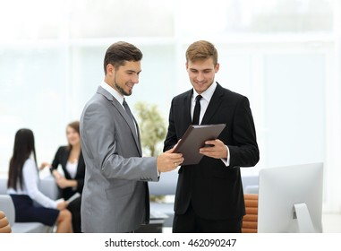 Two successful business partners discussing documents and ideas