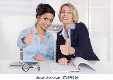 Two successful business women with thumbs up at office.