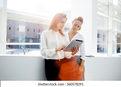 Two successful businesswomen checking list of affairs on digital tablet while standing in office interior, two female partners met in the hallway and stopped for consult new project on touch pad