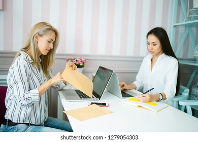 Two successful colleagues are doing their work and wrapping an envelope. Two positive colleagues are talking about their work using laptops and phones in the ofice